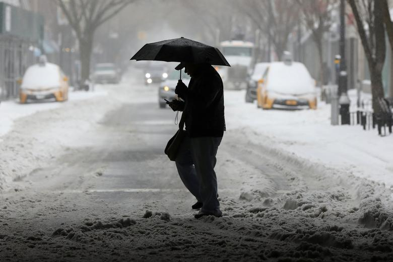 A man walks with an umbrella in the Queens borough of New York, U.S., March 14, 2017. REUTERS/Shannon Stapleton