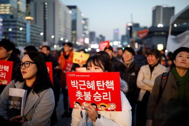 3月15日、韓国は朴槿恵(パク・クネ)大統領の失職に伴う大統領選挙を5月9日に行う。聯合ニュースが報じた。大統領のりめん弾劾による失職を受け、決定を支持する市民ら。ソウル市内中心部で10日撮影(2017年 ロイター/Kim Hong-Ji)