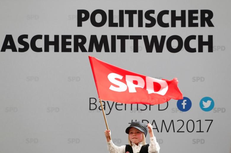 A supporter of Social Democratic Party (SPD) leader Martin Schulz waves a flag during a traditional Ash Wednesday meeting in Vilshofen, Germany, March 1, 2017. REUTERS/Michaela Rehle