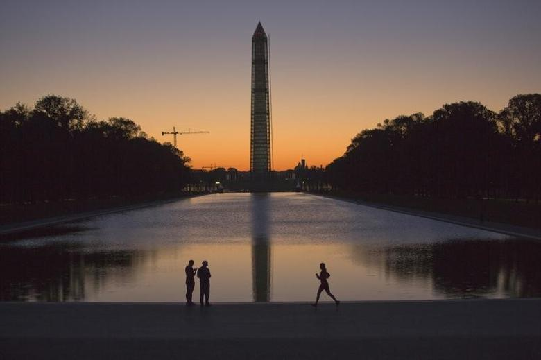 A couple (L) and a jogger pass by the Lincoln Memorial Reflecting Pool before sunrise in Washington, September 24, 2013.  REUTERS/Jason Reed