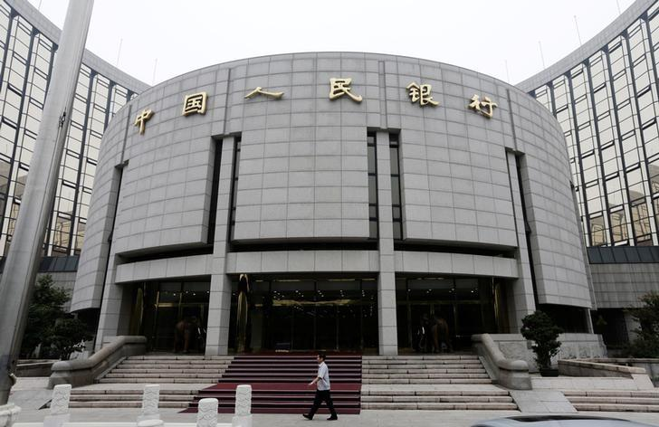A staff member walks in front of the headquarters of the People's Bank of China (PBOC), the central bank, in Beijing, June 25, 2013.   REUTERS/Jason Lee/File Photo