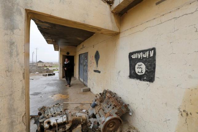 3月16日、トランプ米大統領は、「イスラム国」対策に今後半年間で20億ドル規模の「柔軟な」予算措置を議会に求めている。イスラム国が使用する旗が描かれた壁、イラクで先月9日撮影(2017年 ロイター/Muhammad Hamed)
