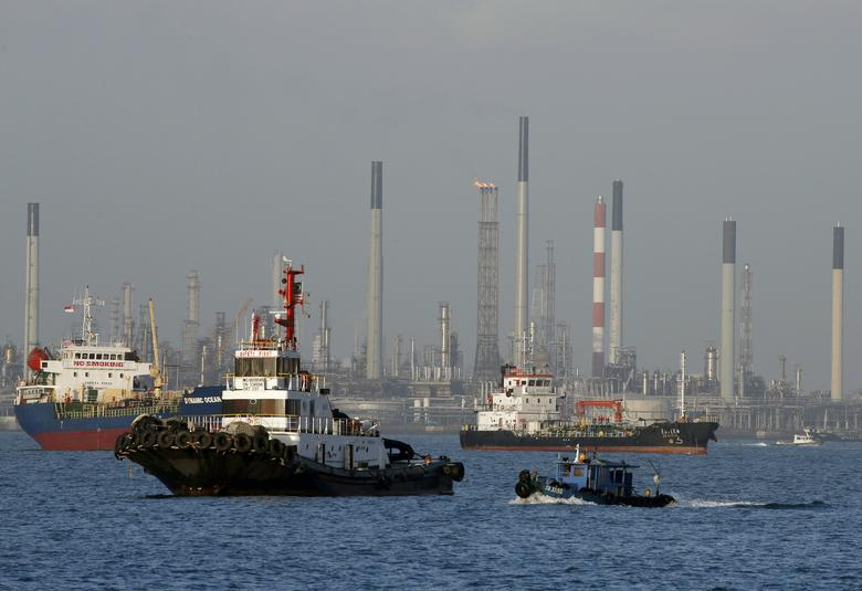 FILE PHOTO:  Vessels pass an oil refinery in the waters off the southern coast of Singapore, February 26, 2016.    REUTERS/Edgar Su/File Photo