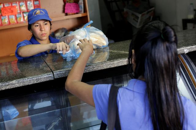 A saleswoman sells bread at a bakery in Caracas, Venezuela March 17, 2017. REUTERS/Marco Bello