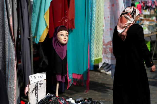 A woman walks past a mannequin wearing an hijab headscarf at a market in the Brussels district of Molenbeek, Belgium, August 14, 2016.  REUTERS/Francois Lenoir/File Photo