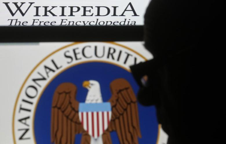 A man is silhouetted near logos of the U.S. National Security Agency (NSA) and Wikipedia in this photo illustration taken in Sarajevo March 11, 2015. REUTERS/Dado Ruvic/File Photo
