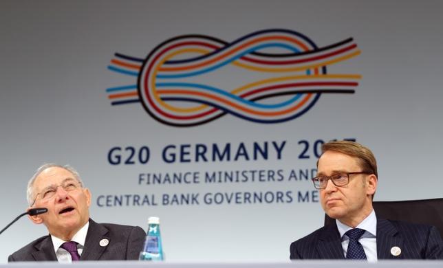3月18日、ドイツのショイブレ財務相(左)は、20カ国・地域(G20)財務相・中央銀行総裁会議では開かれた貿易が経済の耐性強化の鍵とのコンセンサスが広く共有されたとし、反保護貿易主義が明確に打ち出されなかったことを重視しない姿勢を示した。写真は会見するショイブレ財務相とドイツ連邦銀行のワイトマン総裁(2017年 ロイター/Kai Pfaffenbach)