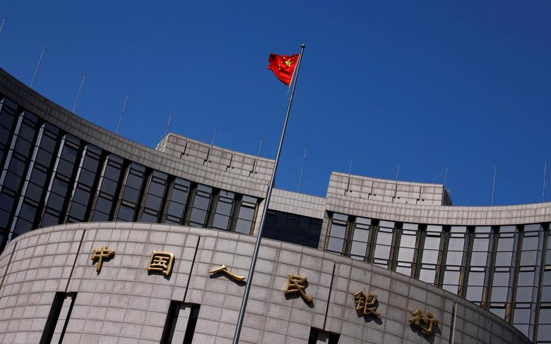 FILE PHOTO: A Chinese national flag flutters outside the headquarters of the People's Bank of China, the Chinese central bank, in Beijing, China April 3, 2014.   REUTERS/Petar Kujundzic/File Photo