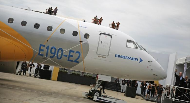 Brazilian aircraft maker Embraer's CEO Frederico Curado (R) salutes workers next to an new Embraer E190-E2 during its unveil in Sao Jose dos Campos, Brazil, February 25, 2016. REUTERS/Nacho Doce