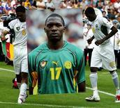 لاعبان بمنتخب الكاميرون يحملان صورة اللاعب الراحل مارك فيفيان فويه التي توفي خلال كأس القارات 2003