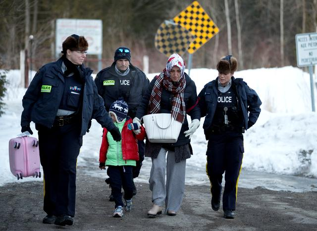 A family that claimed to be from Turkey are met by Royal Canadian Mounted Police (RCMP) officers after they crossed the U.S.-Canada border illegally leading into Hemmingford, Quebec Canada March 20, 2017.  REUTERS/Christinne Muschi