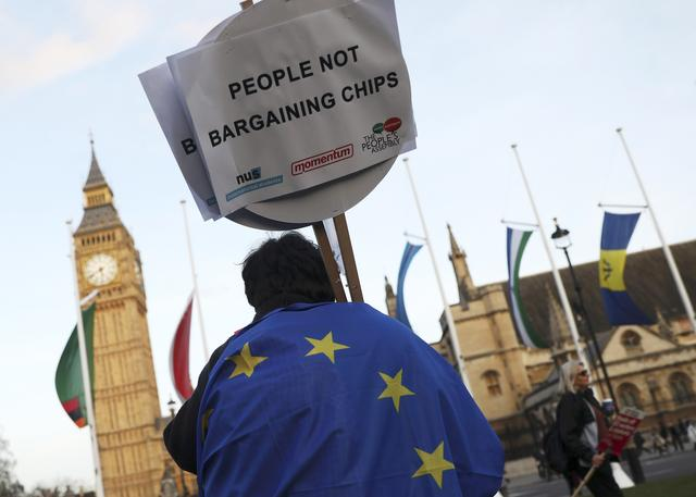 FILE PHOTO - A demonstrator holds a placard during a protest in favour of amendments to the Brexit Bill outside the Houses of Parliament, in London, Britain, March 13, 2017. REUTERS/Neil Hall/File Photo