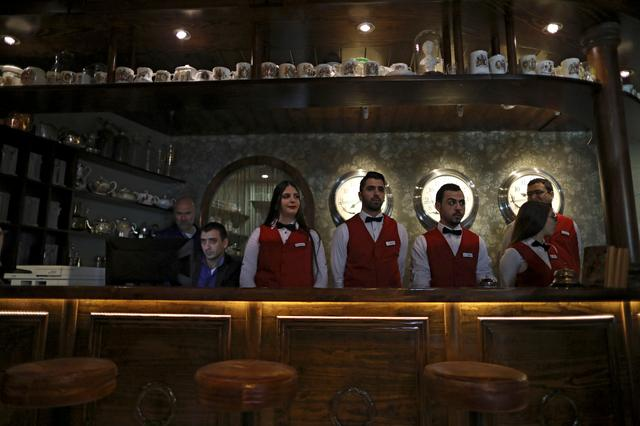 Waiters and waitresses stand in the Walled Off hotel which was decorated by street artist Banksy, after it was opened for guests to do check-in in the West Bank city of Bethlehem March 20, 2017. REUTERS/ Ammar Awad