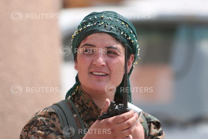 A female Kurdish fighter from the People's Protection Units (YPG) carries a walkie-talkie as she stands in the Ghwairan neighborhood of Hasaka, Syria, August 22, 2016. REUTERS/Rodi Said