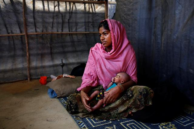 Asmot Ara, 18, holds her seven-day-old unnamed daughter as she poses for a photograph inside their shelter in Balukhali unregistered refugee camp in Cox's Bazar, Bangladesh, February 8, 2017. REUTERS/Mohammad Ponir Hossain