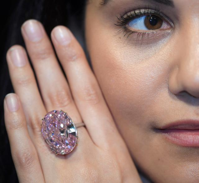 A model poses with a 59.60-carat mixed cut diamond known as ''The Pink Star'', the largest Internally Flawless Fancy Vivid Pink diamond ever graded by the Geological Institute of America (GIA), ahead of being auctioned in Hong Kong next month by Sotheby's which said it could fetch upwards of $60 million (GBP £48.4 million) to make it the most expensive diamond of its kind ever sold, in London, Britain, March 20, 2017.  REUTERS/Toby Melville