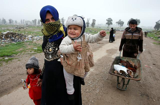 Displaced Iraqi people from different areas in Mosul flee their homes to reach safe areas after clashes broke out as Iraqi forces battle with Islamic State militants in the city of Mosul. REUTERS/Youssef Boudlal