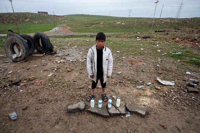 A boy sells milk on the street near the city of Mosul. REUTERS/Youssef Boudlal