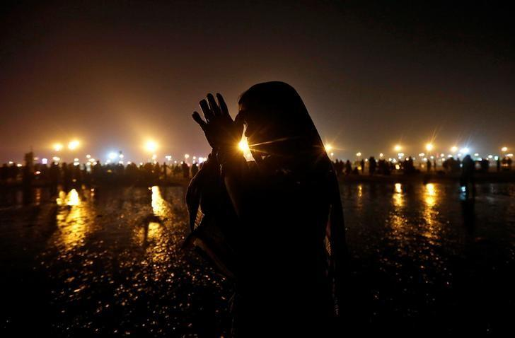 A Hindu pilgrim offers prayers after taking a dip in the Ganges river ahead of the one-day festival of Makar Sankranti, at Sagar Island, south of Kolkata, India January 13, 2017. REUTERS/Rupak De Chowdhuri