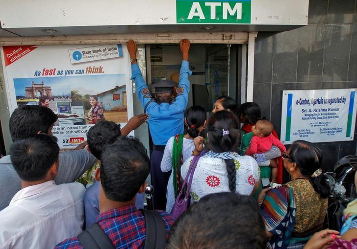 A security guard closes the shutter of State Bank of India ATM after it stopped dispensing cash in Agartala, India, November 15, 2016. REUTERS/Jayanta Dey/Files