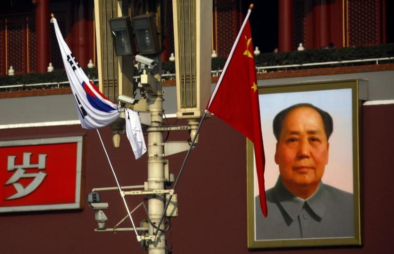 FILE PHOTO: South Korean and Chinese national flags hang from a pole in front of the giant portrait of former Chinese chairman Mao Zedong at Beijing's Tiananmen Square January 9, 2012.  REUTERS/David Gray