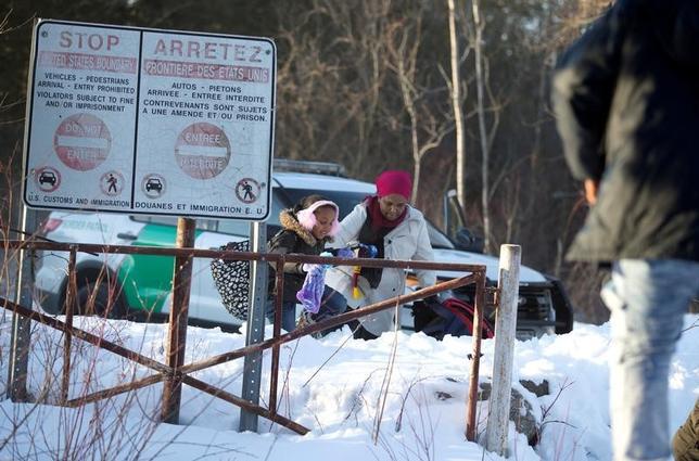 3月22日、米政権の移民制限により、高度な技術や専門知識を持つ有能な人材は今後、より寛大な受け入れ国カナダへと流れるだろう。写真は、米国との国境を違法に越えてカナダのケベック州に入るスーダン出身とみられる家族。20日撮影(2017年 ロイター/Christinne Muschi)