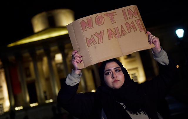 A woman holds a placard at a vigil in Trafalgar Square the day after an attack in London, Britain, March 23, 2017. REUTERS/Hannah McKay