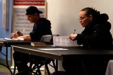 Unas personas rellenando unas aplicaciones de empleo en una feria laboral en Denver, EEUU, feb 15, 2017. El número de estadounidenses que presentaron nuevas solicitudes de subsidios por desempleo subió inesperadamente la semana pasada, pero permaneció debajo de en niveles asociados a un fortalecimiento del mercado laboral.   REUTERS/Rick Wilking