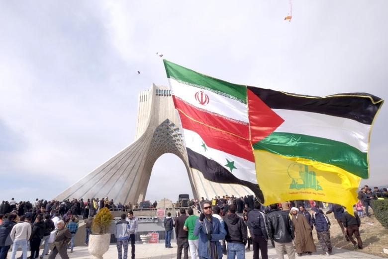 A man carries a giant flag made of flags of Iran, Palestine, Syria and Hezbollah, during a ceremony marking the 37th anniversary of the Islamic Revolution, in Tehran February 11, 2016. REUTERS/Raheb Homavandi/TIMA