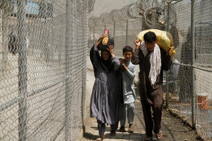 A family coming from Afghanistan walk down a corridor between security fences at the border post in Torkham, Pakistan June 18, 2016. REUTERS/Fayaz Aziz/Files