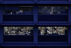 Los oficinistas trabajando son fotografiados en oscuridad en Tokio, Japón. 3 de marzo 2015. Una gran mayoría de las firmas japonesas dijo que aumentará los salarios en el 2017 a un ritmo más lento que el año pasado, según un sondeo de Reuters, un revés para los intentos del primer ministro Shinzo Abe por impulsar a la economía a través de unos mayores sueldos.  REUTERS/Issei Kato/File Photo