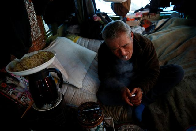 Homeless Makoto Shinbo smokes a cigarette at his makeshift house in Miyashita park in Tokyo, Japan, February 17, 2017. REUTERS/Kim Kyung-Hoon