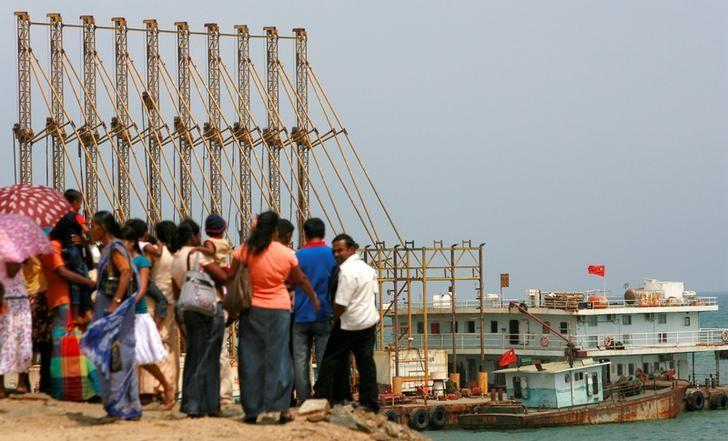 A group of Sri Lankan visitors at the new deep water shipping port watch Chinese dredging ships work in Hambantota, 240 km (150 miles) southeast of Colombo, March 24, 2010.  REUTERS/Andrew Caballero-Reynolds/Files