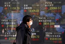 En la imagen, un hombra pasa ante un letrero electrónico que muestra la cotización del Nikkei, el Dow Jones y otros índices en una casa de valores de Tokio, el 26 de enero de 2017.El índice Nikkei de la bolsa de Tokio rebotó el martes desde un mínimo en más de seis semanas luego de que un repunte del yen se detuvo. REUTERS/Kim Kyung-Hoon