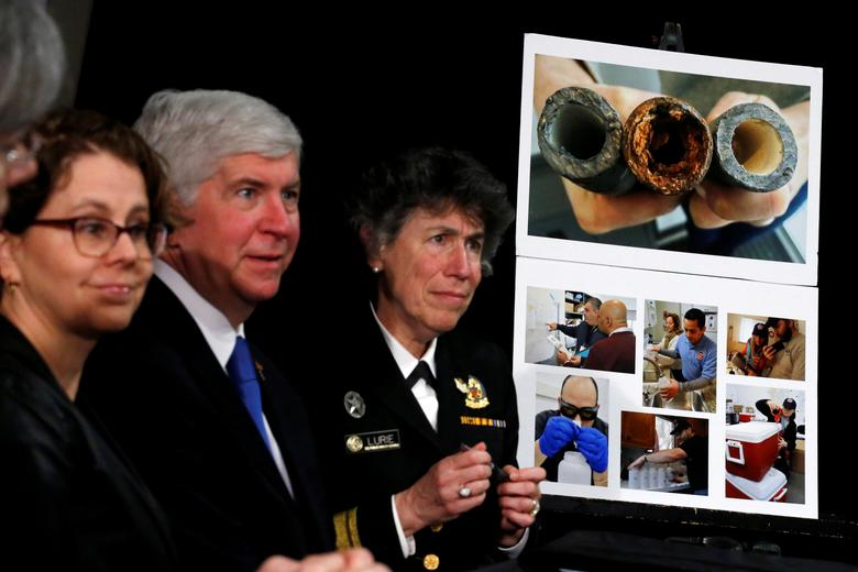 FILE PHOTO: A picture of damaged pipes from Flint, a city struggling with the effects of lead-poisoned drinking water, is seen as Michigan Governor Rick Snyder (2-L) attends a meeting between local and federal authorities with U.S. President Barack Obama, in Flint, Michigan, U.S., May 4, 2016.  REUTERS/Carlos Barria/File Photo