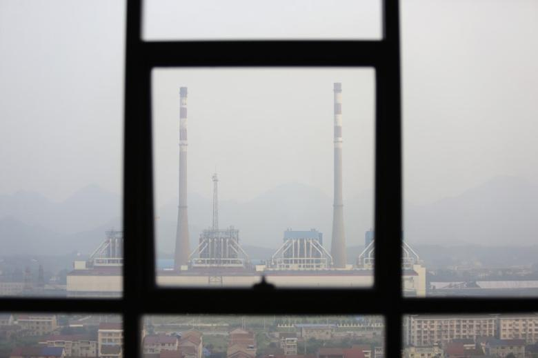 Chimneys are seen through a window at a coal-fired power plant on a hazy day in Shimen county, central China's Hunan Province, June 2, 2014. REUTERS/Jason Lee