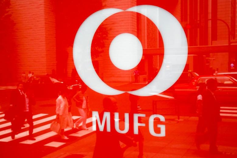 People are reflected in the logo of Mitsubishi UFJ  Financial Group's bank of Tokyo-Mitsubishi UFJ (MUFG) in Tokyo, Japan, May 16, 2016. REUTERS/Thomas Peter