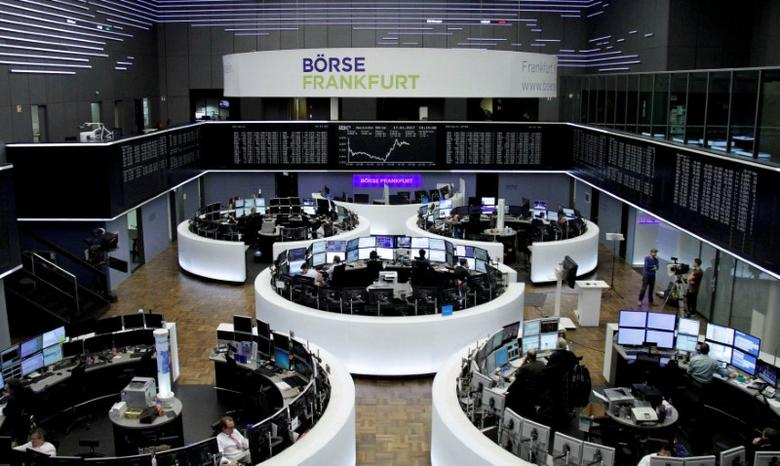 FILE PHOTO:  Traders work at their desks in front of the German share price index, DAX board, at the stock exchange in Frankfurt, Germany, January 17, 2017.    REUTERS/Staff/Remote/File Photo