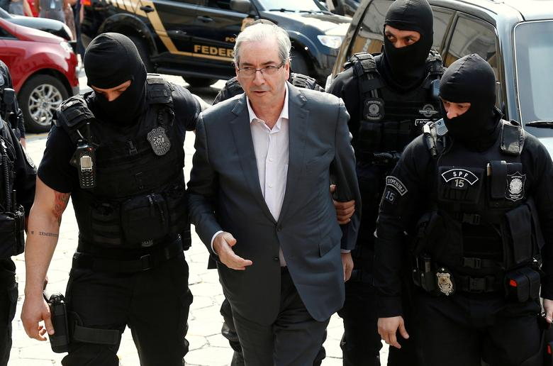 FILE PHOTO - Former speaker of Brazil's Lower House of Congress, Eduardo Cunha (C), is escorted by federal police officers as he arrives to the Institute of Forensic Science in Curitiba, Brazil, October 20, 2016. REUTERS/Rodolfo Buhrer/File Photo