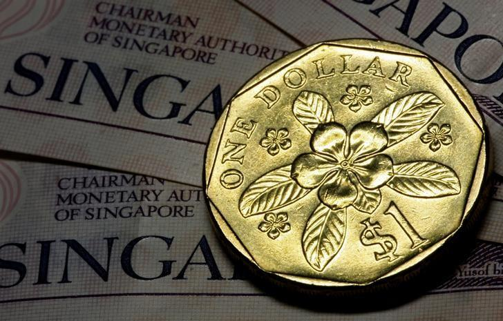 FILE PHOTO -  A Singapore one dollar coin rests on top of Singapore two dollar notes in this April 13, 2010 photo illustration.  REUTERS/Tim Chong/File Photo