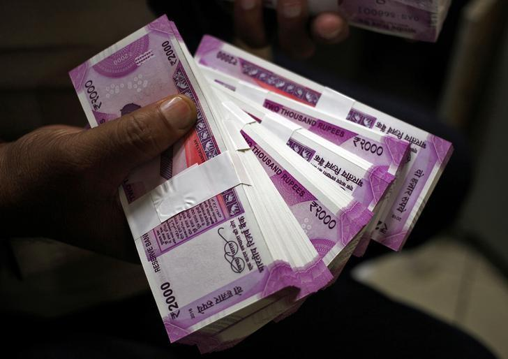 FILE PHOTO: A cashier displays the new 2000 Indian rupee banknotes inside a bank in Jammu, November 15, 2016. REUTERS/Mukesh Gupta/File photo