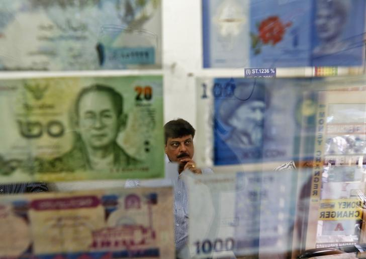 A man watches television inside his currency exchange shop in New Delhi August 30, 2013. REUTERS/Mansi Thapliyal/File Photo
