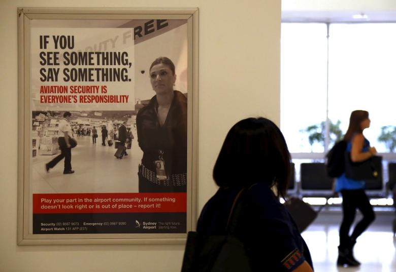FILE PHOTO: A poster regarding airport security hangs from a wall as passengers walk around the departures area at Sydney International Airport, Australia, March 23, 2016.  REUTERS/David Gray