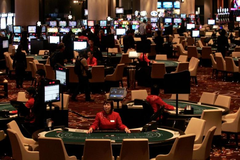 FILE PHOTO -  Dealers wait for customers at the casino inside Melco Crown Entertainment's latest gaming resort City of Dreams in Macau June 1, 2009.   REUTERS/Tyrone Siu/File Photo