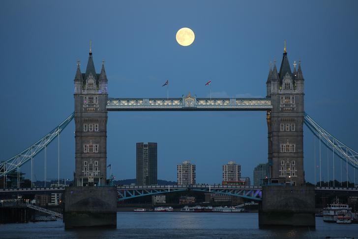 资料图片:2014年8月,一轮明月升至伦敦塔桥上方天空。REUTERS/Paul Hackett