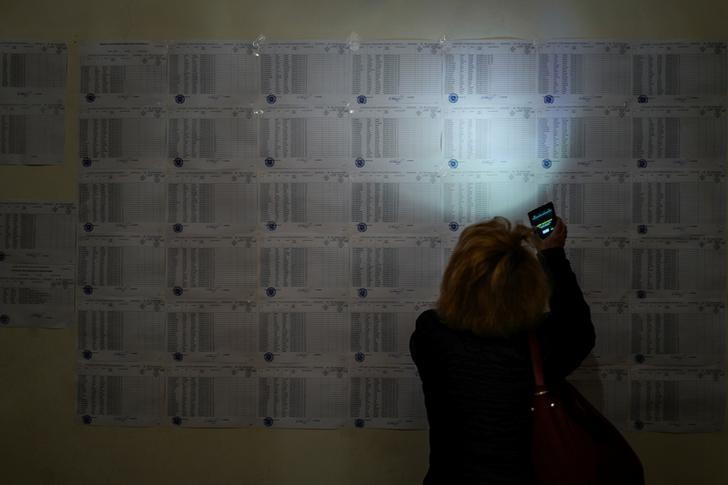 A woman uses her mobile phone to read voters list during a parliamentary election at a poling station in Yerevan, Armenia, April 2, 2017. Vahan Stepanyan/PAN Photo/Handout via REUTERS