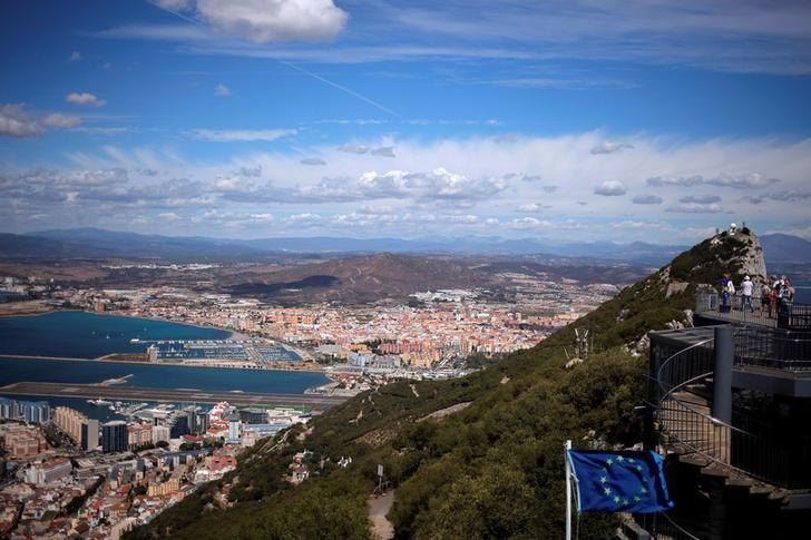 A general view shows the Spanish city of La Linea de la Concepcion (rear) and the tarmac of the Gibraltar International Airport (bottom L) while tourists stand on the top of the Rock (R) next to the European Union flag, in the British overseas territory of Gibraltar, September 14, 2016. REUTERS/Jon Nazca/File Photo