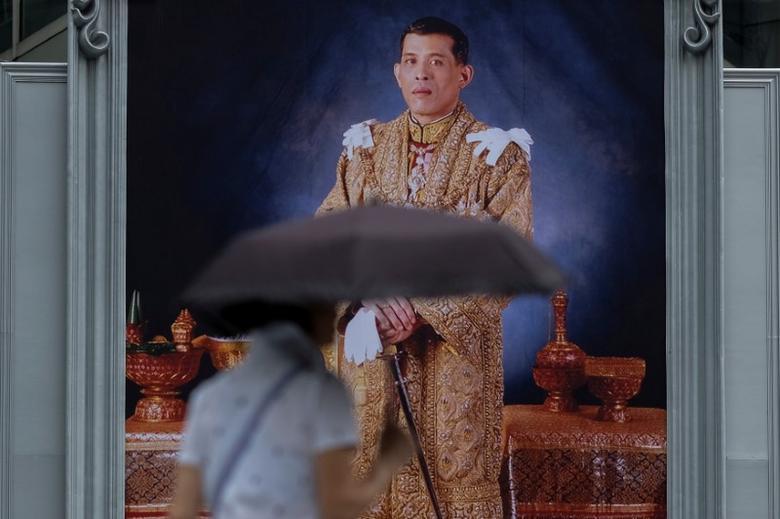 FILE PHOTO -  A woman walks past a portrait of Thailand's King Maha Vajiralongkorn Bodindradebayavarangkun at a department store in central Bangkok, Thailand January 13, 2017.