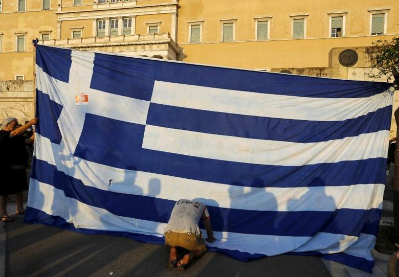 A protester kneels to pay his respect in front of a Greek flag during an anti-austerity rally in Athens, Greece, June 29, 2015. REUTERS/Yannis Behrakis