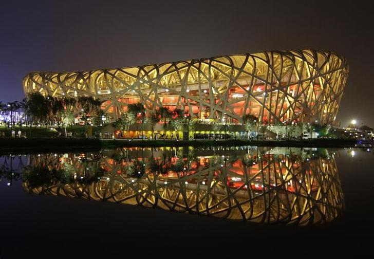 The National Stadium, also known as the Bird's Nest, is seen reflected in water at night in Beijing August 5, 2008. REUTERS/David Gray/File Photo